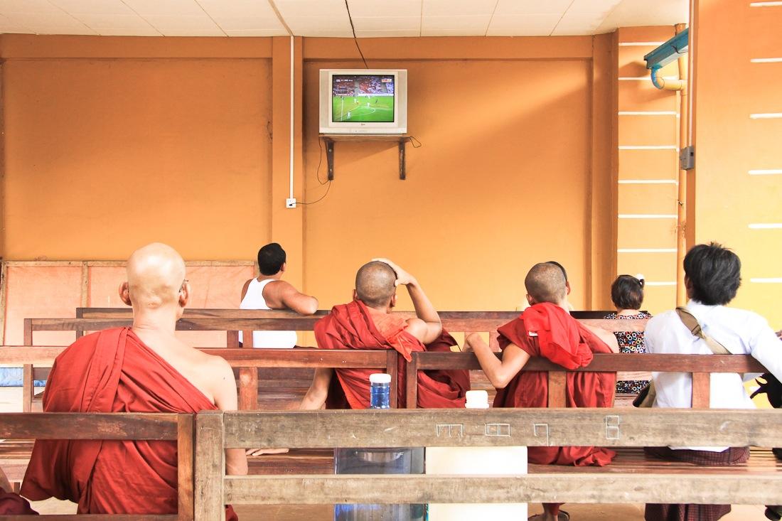 en attendant le camion qui nous mènera au Rocher d'or en Birmanie, les moines regardent le foot dans la salle d'attente