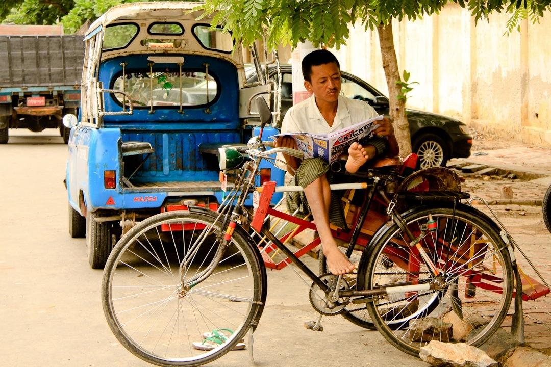 Nous sommes à Mandalay en Birmanie. Ce monsieur attend le client en lisant la presse propagande