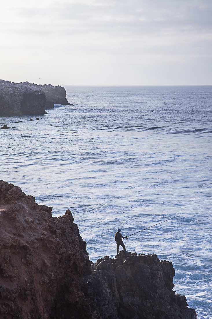 Le pêcheur de Carrapateira à flanc de falaise et proche des vagues