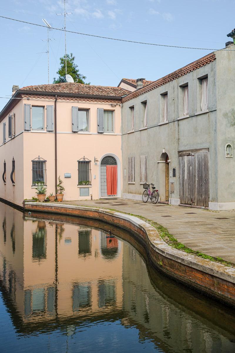 Vélo, rideau, vierge et maison colorée, c'est une scène normale de la vie à Comacchio en Italie